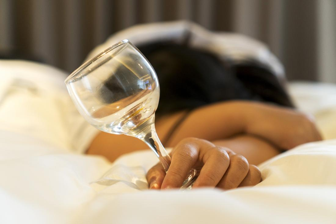 a woman on the bed holding a glass of wine